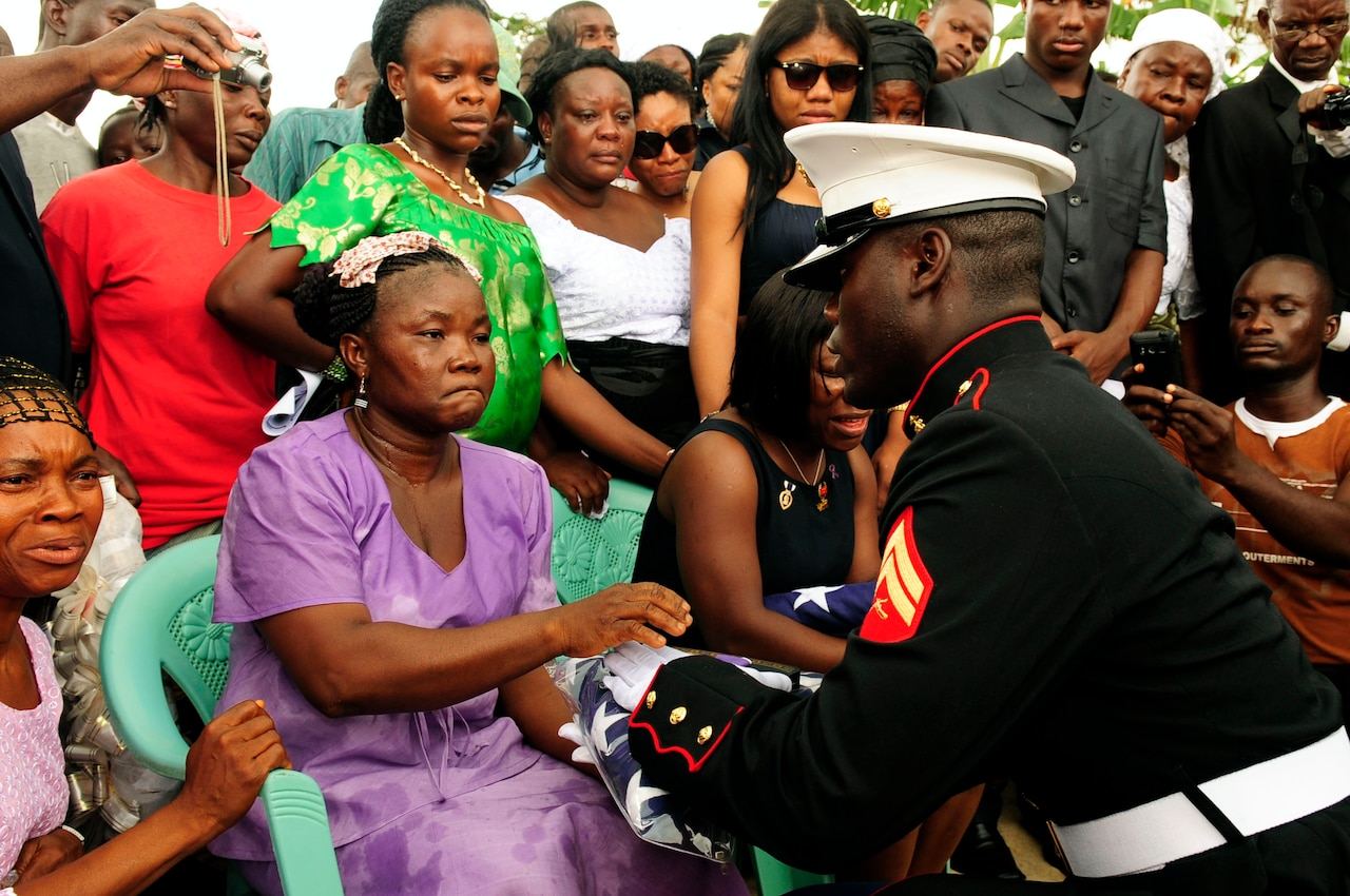 A U.S. Marine hands a folded American flag to a grieving woman sitting in a chair; she is surrounded by other people.