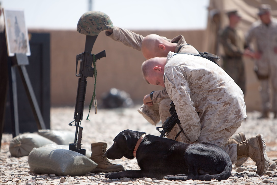 Two Marines kneel and bow their heads in front of an empty boot, helmet and rifle that are propped up in remembrance of a fallen Marine. Beside them, a black dog sits on the ground.