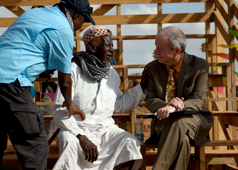 U.S. Ambassador to Djibouti Larry André, right, speaks with a Chabelly village elder at the grand opening of the Chabelly Village soccer field in Chabelly, Djibouti, Dec. 30, 2019. U.S. service member volunteers constructed the soccer field. (U.S. Air Force photo by Staff Sgt. J.D. Strong II)