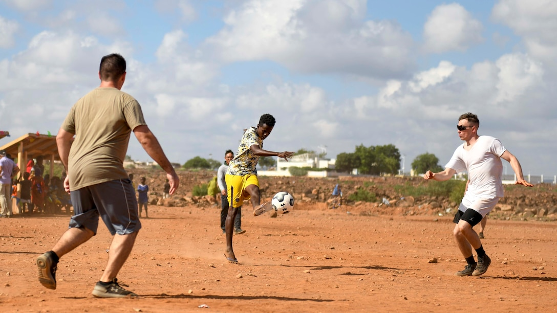 U.S. service members play a game of soccer with Chabelly villagers during the grand opening of the Chabelly Village soccer field in Chabelly, Djibobuti, Dec. 30, 2019. U.S. service member volunteers constructed the soccer field. (U.S. Air Force photo by Staff Sgt. J.D. Strong II)