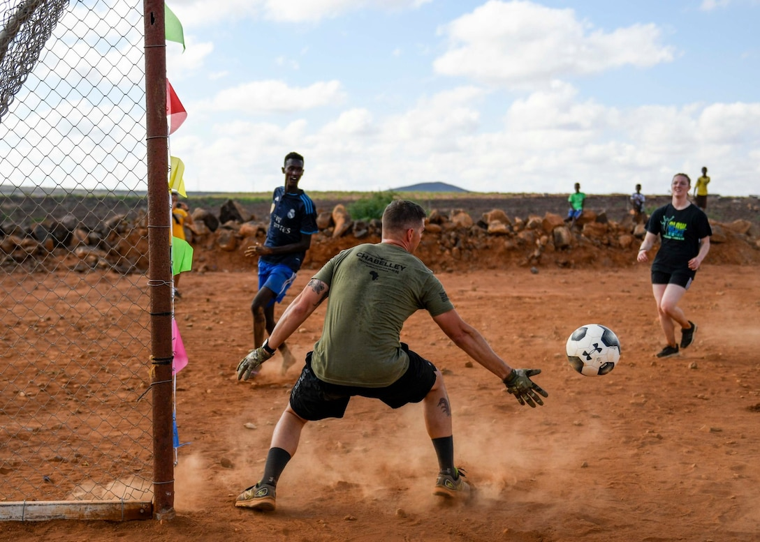 U.S. service members play a game of soccer with Chabelley villagers during the grand opening of the Chabelley Village soccer field in Chabelley, Djibobuti, Dec. 30, 2019. U.S. service member volunteers constructed the soccer field. (U.S. Air Force photo by Staff Sgt. J.D. Strong II)