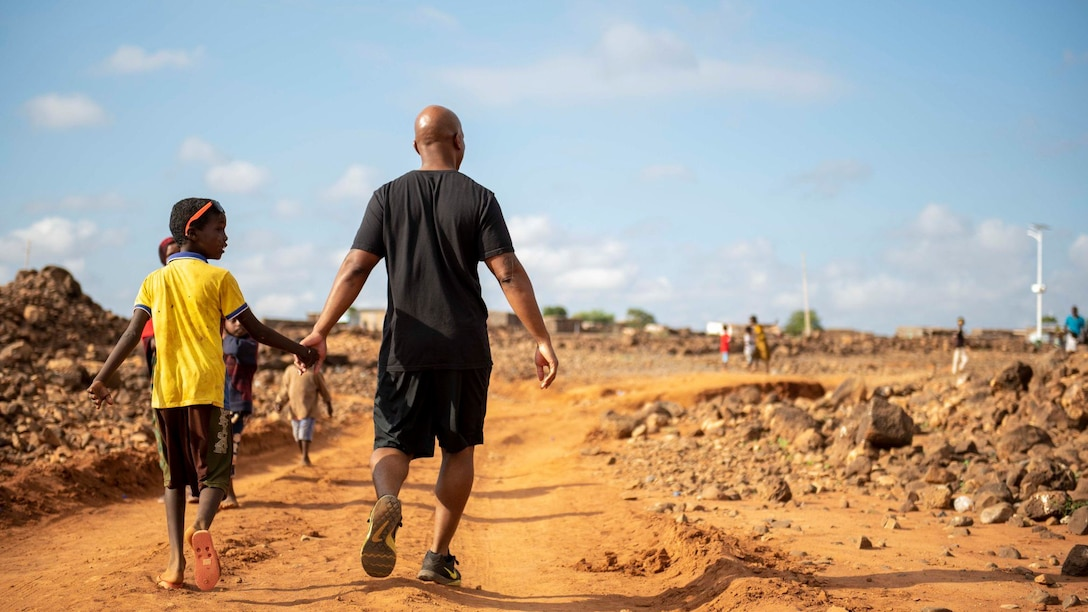 A U.S. service member walks with a Chabelley village youth during the grand opening of the Chabelley Village soccer field in Chabelley, Djibobuti, Dec. 30, 2019. U.S. service member volunteers constructed the soccer field. (U.S. Air Force photo by Staff Sgt. J.D. Strong II)