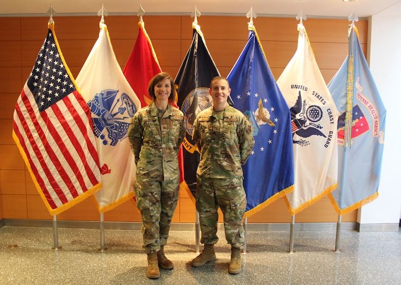 Image of two Airmen standing in front of flags.