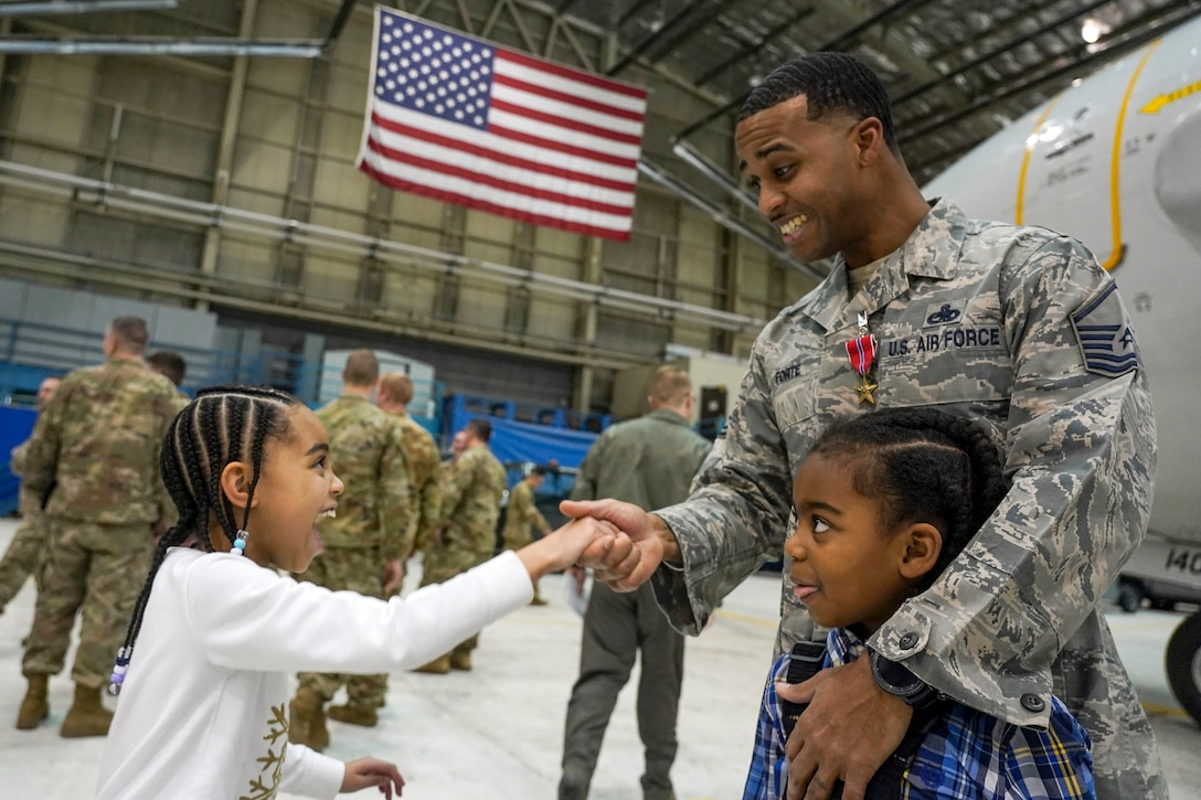 A smiling airman wearing a medal shakes hands with his smiling daughter while hugging his son in a hangar.