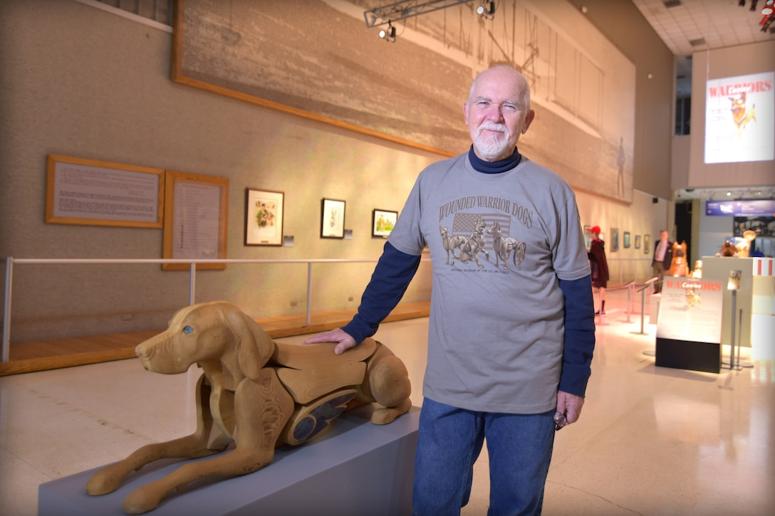 Artist James Mellick stands next to one of his dog sculptures.
