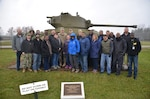 A group of men and women from the DLA RDT Red and White Teams pose in front of a tank during training at Camp Atterbury, Indiana.
