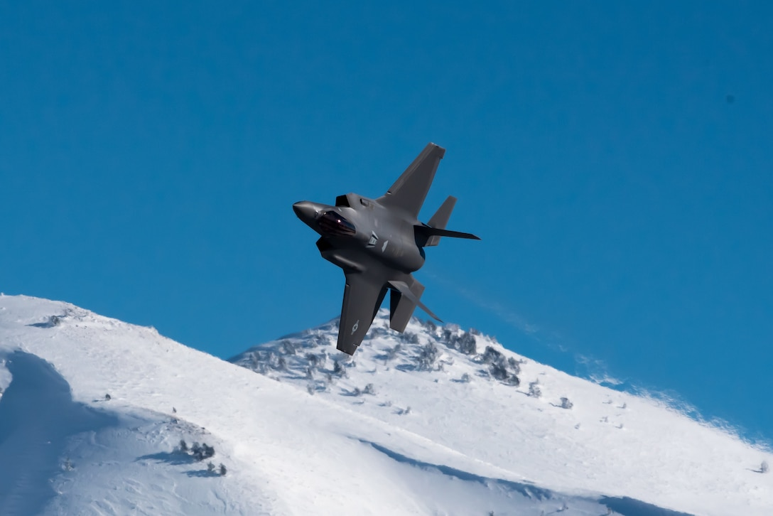 A military aircraft flies almost upside down above snowy mountains.