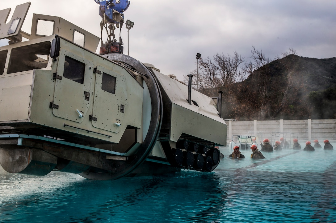 A large mock vehicle hangs above a pool where Marines gather at one end.