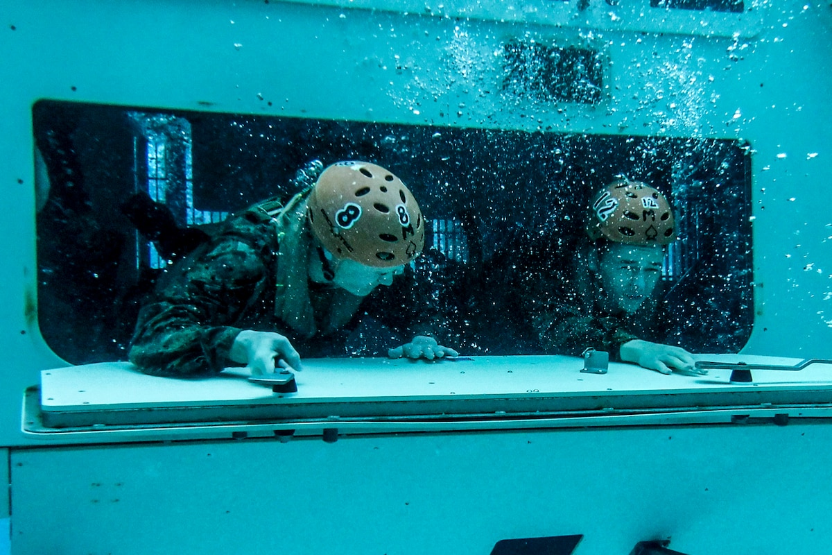 Two Marines wearing helmets exit from a metal opening of a piece of equipment under water in a pool.