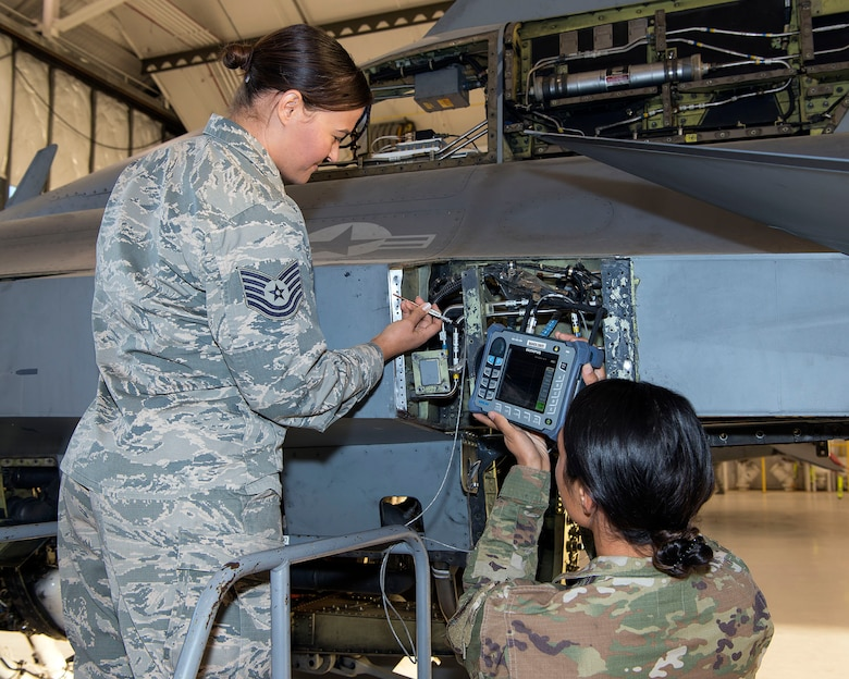 two female Airmen inspect F-16