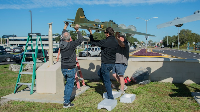 Gino Galvez (left), an Atlantic-Models scale model manufacturer, Stephen Ove (center), the 6th Air Refueling Wing historian and Roger Jarman (right), the Atlantic-Models vice president, lift a scale model of the Memphis Belle, a B-17 Flying Fortress onto a display-stand Jan. 8, 2020, at MacDill Air Force Base, Fla.  The Memphis Belle was stationed at MacDill AFB in 1942, went on to complete 25 combat missions against Nazi Germany. (U.S. Air Force photo by Airman 1st Class Shannon Bowman)