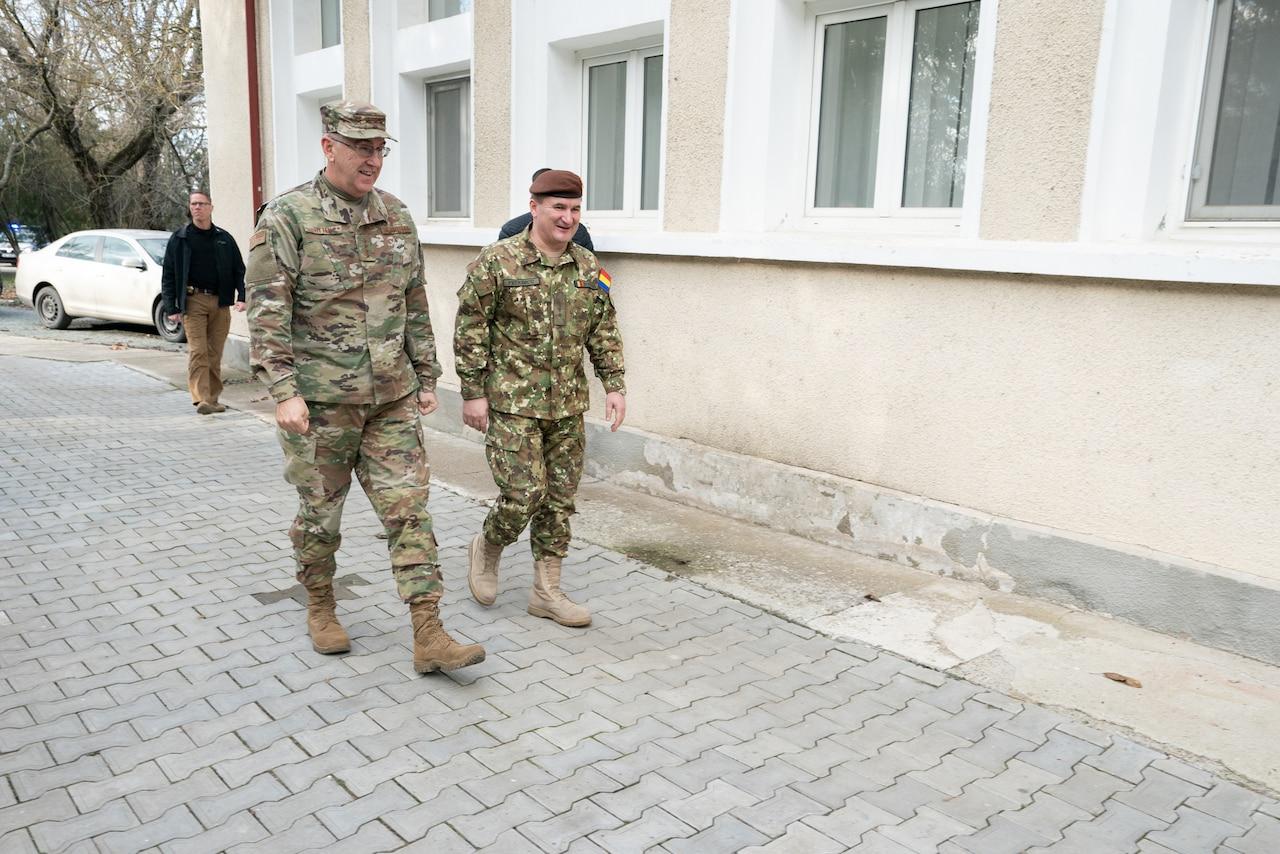 Two men walk outside a building.