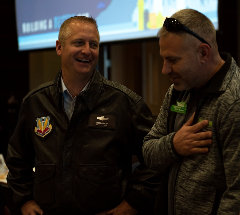 U.S. Air Force Col. Brian Laidlaw, 325th Fighter Wing commander, laughs with a local community member at the Bay County Chamber of Commerce monthly meeting at Panama City, Florida, Jan. 10, 2020. Laidlaw, along with U.S. Air Force Col. Travis Leighton, Tyndall Program Management Office director, and U.S. Navy Cmdr. Kevin Christenson, Naval Support Activity Panama City commanding officer, attended the First Friday meeting as representatives of military communities in the local area. (U.S. photo by Staff Sgt. Magen M. Reeves)