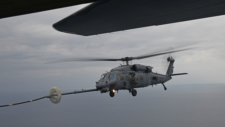 An HH-60G Pave Hawk assigned to the 33rd Rescue Squadron performs helicopter air-to-air refueling with an MC-130J Commando II from the 17th Special Operations Squadron above the Pacific Ocean during Exercise Westpac Rumrunner Jan. 10, 2020. Westpac Rumrunner represents an evolution of 18th Wing assets and capability to work with joint partners in defense of American allies and to ensure a free and open Indo‐Pacific. (U.S. Air Force photo by Staff Sgt. Benjamin Sutton)