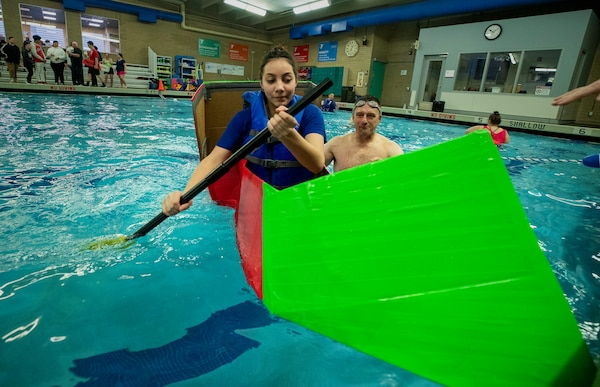 Stephen Mastel, PSNS & IMF STEM outreach coordinator provides in-water support for an eight-grade applied math student from Mountain View Middle School as she paddles her boat during the school's inaugural cardboard boat race at the Bremerton Family YMCA. Twenty students participated in the event, piloting self-constructed boats made of cardboard and duct tape.