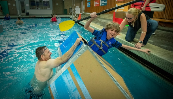 Corrine Beach, PSNS & IMF STEM coordinator and NAVSEA student engagement lead and Stephen Mastel, PSNS & IMF STEM outreach coordinator help an eight-grade applied math student from Mountain View Middle School steady his boat during the school's inaugural cardboard boat race at the Bremerton Family YMCA. Twenty students participated in the event, piloting self-constructed boats made of cardboard and duct tape.