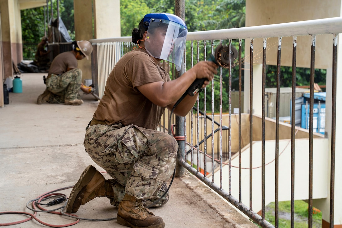 Sailors wearing protective headwear use tools to work on metal guardrails.