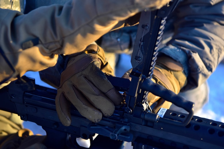 Two 354th Security Forces Squadron Airmen load a M-249 Squad Automatic Weapon with prototype cold weather gloves at Eielson Air Force Base, Alaska, Jan. 9, 2020. Even in minus 40 degrees, Security Forces Airmen must be able to use their hands to operate their weapon systems. (U.S. Air Force photo by Senior Airman Beaux Hebert)