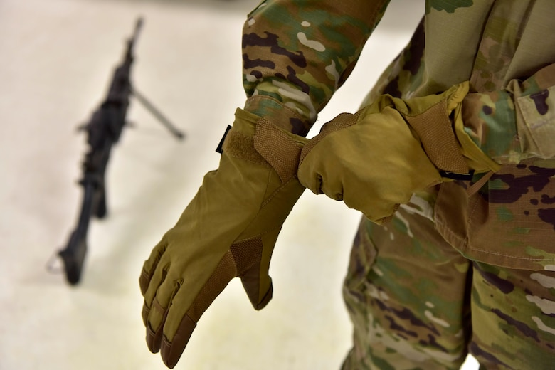 Airman 1st Class Dawson Koett, 354th Security Forces Squadron installation entry controller, dons a new type of gloves at Eielson Air Force Base, Alaska, Jan. 9, 2020. The 354th SFS partnered with the U.S. Army Combat Capabilities Developmental Command to try out new cold weather gear. (U.S. Air Force photo by Senior Airman Beaux Hebert)