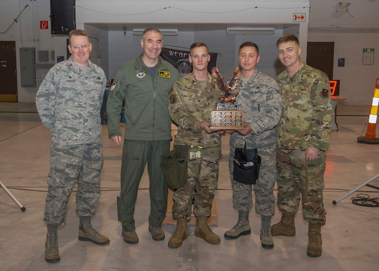 Col. Joseph Campo, 49th Wing commander (second from left), and Col. Tim Harbor, 49th Maintenance Group commander, present the first place trophy to weapons load crew members from the 314th Fighter Squadron during the fourth quarter load competition awards ceremony, Jan. 10, 2020, on Holloman Air Force Base, N.M. 12 Airmen from the 9th Aircraft Maintenance Unit, 29th AMU, 314th FS and 311th FS competed to see who could load munitions onto their respective aircraft the fastest. (U.S. Air Force photo by Airman 1st Class Quion Lowe)