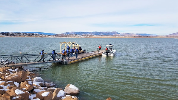Volunteers (in blue) prepare to board a boat to help count eagles from the lake during the annual eagle watch at Abiquiu Lake, Jan. 4, 2020. This year, 66 volunteers participated in counting eagles from three stationary positions on shore and two boats on the lake.