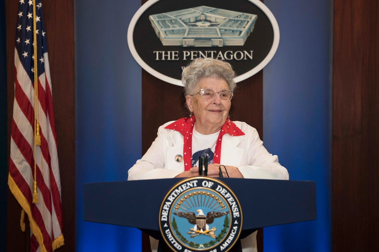 A woman stands at a lectern with the DOD logo.