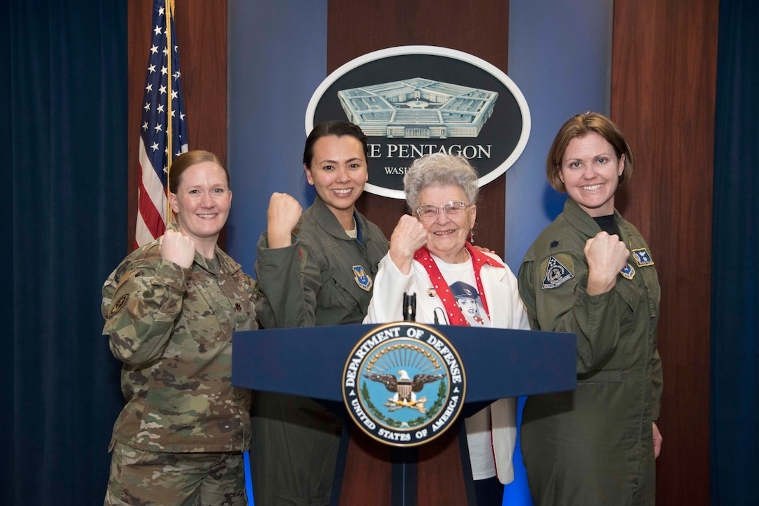 Three service members and a civilian flex their biceps behind a lectern.