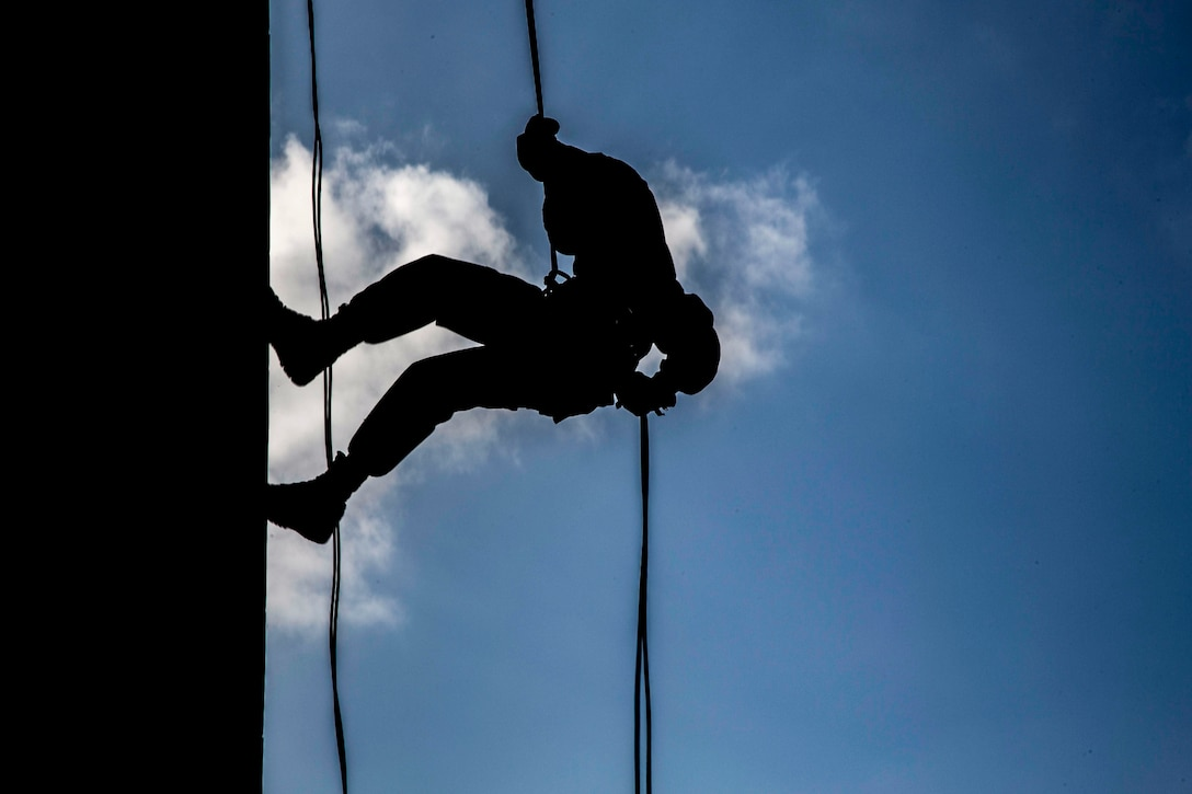 A Marine, shown in silhouette, rappels down a wall against a blue cloud-streaked sky.