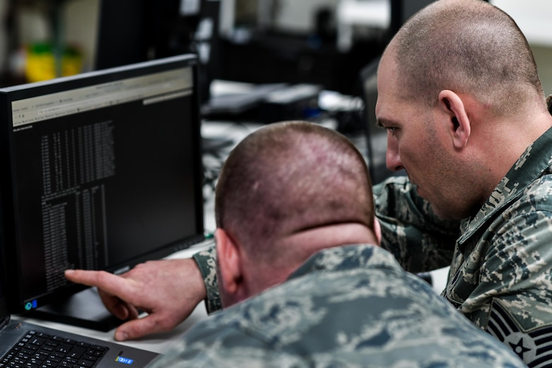 Tech Sgt. Scott Ranostay, a cyber systems operator, and Tech Sgt. Lawrence Mulder, a communications computer systems operator, both assigned to the 910th Communications Squadron, troubleshoot their lab environment with a Cyber Vulnerability Assessment Hunt weapon system, Jan. 11, 2019, at Youngstown Air Reserve Station.