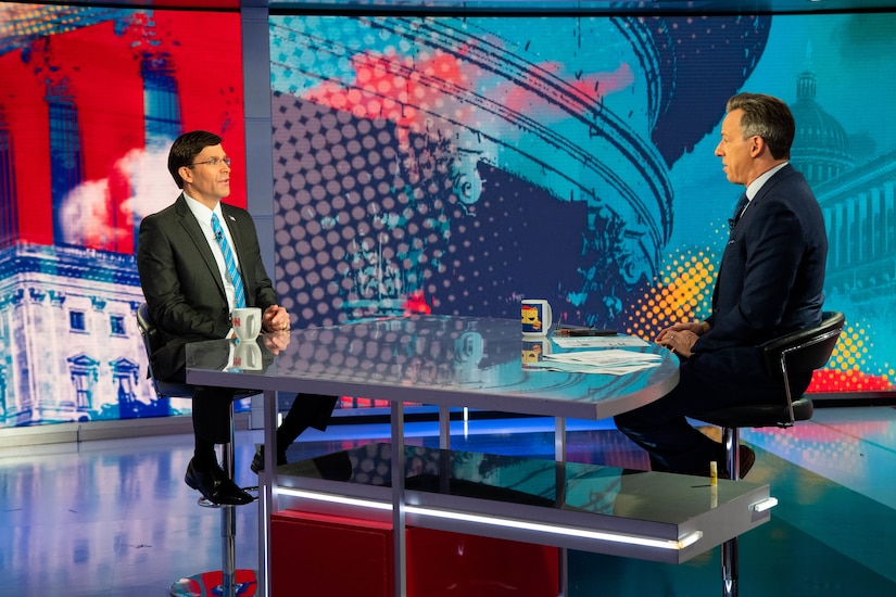 Defense Secretary Dr. Mark T. Esper sits across a table from another civilian inside a television studio.