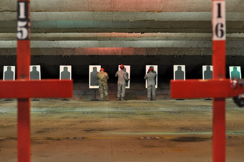 From left, Senior Airman Emilio San Miguel, Master Sgt. Henry Relf and Tech. Sgt. Shannon Jones, 908th Security Forces Squadron Combat Arms instructors, stand in front of the targets, Nov. 2, 2019, in the firing bay at Maxwell AFB, Alabama. After every round of firing, the instructors secure the lanes so that they can review each target in order to instruct Airmen on how to improve. (U.S. Air Force photo by Airman 1st Class Shelby S. Thurman)