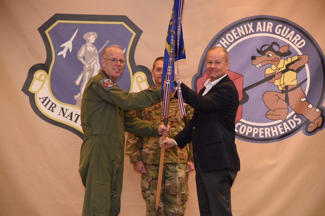 Col. John Rummel, 161st Air Refueling Wing Medical Group Squadron commander, passes the guidon to Mr. Steve Purves during the Honorary Commander Induction ceremony, Nov. 2. During the ceremony, six honorary commanders were inducted. (U.S. Air National Guard photo by Tech. Sgt. Anthony Reynolds)