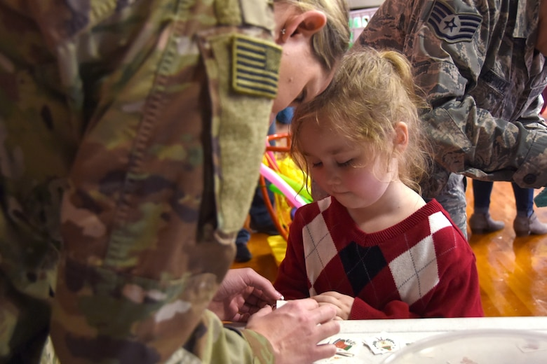 A young student of Badin Elementary School (B.E.S.) selects a temporary hand tattoo during Operation Santa held at B.E.S., Badin, N.C., Dec. 14th, 2019.  Operation Santa is an annual event run by the Chapter 7 organization of the North Carolina Air National Guard (NCANG) which chooses select schools to provide assistance to families during the holiday season. This year, the NCANG provided presents, lunch, music, bouncy castles and a Santa. The NCANG also partnered with the local Target for food donations.