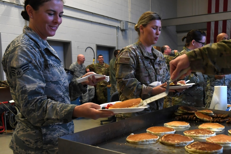 North Carolina Air National Guardsmen are served pancakes hot from the grill during a breakfast fundraiser, Jan. 12, 2020 at the 235th Air Traffic Control Squadron in New London, N.C. Members of the North Carolina Air National Guard as well as local airport authorities and law enforcement were invited to participate in a pancake breakfast social in order to strengthen community ties and build new relationships while raising funds for Morale, Welfare and Recreation.