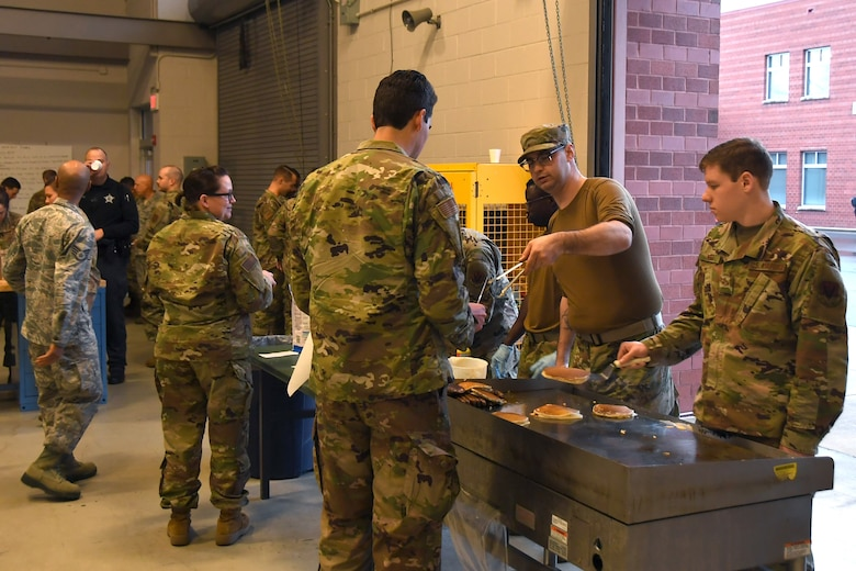 U.S. Air Force Senior Airman Robert Hartley (left), and other Airmen cook pancakes on a grill during a breakfast fundraiser, Jan. 12, 2020 at the 235th Air Traffic Control Squadron in New London, N.C. Members of the North Carolina Air National Guard as well as local airport authorities and law enforcement were invited to participate in a pancake breakfast social in order to strengthen community ties and build new relationships while raising funds for Morale, Welfare and Recreation.