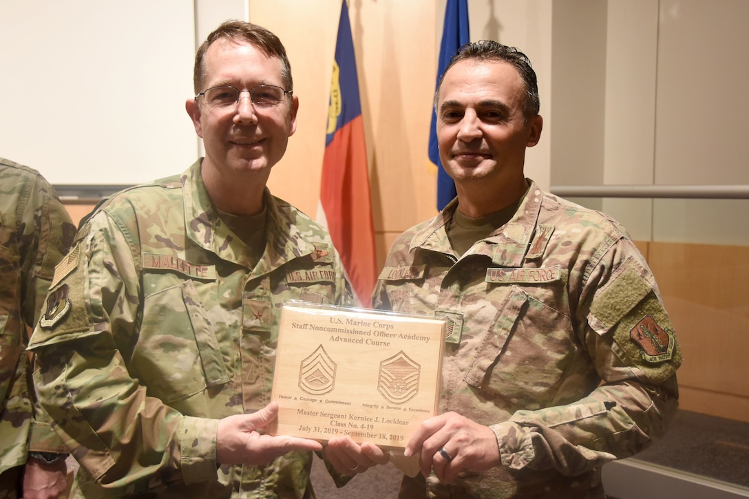 U.S. Air Force North Carolina Assistant Adjutant General for Air, Brig. Gen. Stephen Mallette (left), presents Master Sgt. Kernice Locklear, 263rd Combat Communications Squadron (right), with an award during an all-call held at the New London, N.C. Air National Guard Base (NCANG) headquarters, Jan. 12, 2020. Members of the NCANG celebrated the accomplishments of Master Sgt. Judd Locklear who attended the United States Marine Corps Staff Non-Commissioned Officer Academy last year in an effort to better understand the traditions and customs of a sister service. Since attending the academies, Locklear has implemented U.S. Marine Corps. practices such as sharing unit history and helping newer Airmen feel more involved with more responsibilities.