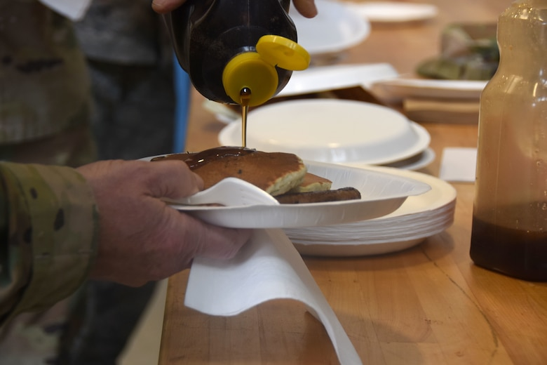 U.S. Air Force Assistant Adjutant General for Air, Brig. Gen. Stephen Mallette, pours syrup over his pancakes during a breakfast, Jan. 12, 2020 at the 235th Air Traffic Control Squadron in New London, N.C. Members of the North Carolina Air National Guard as well as local airport authorities and law enforcement were invited to participate in a pancake breakfast fundraiser in order to strengthen community ties and build new relationships while raising funds for Morale, Welfare and Recreation.