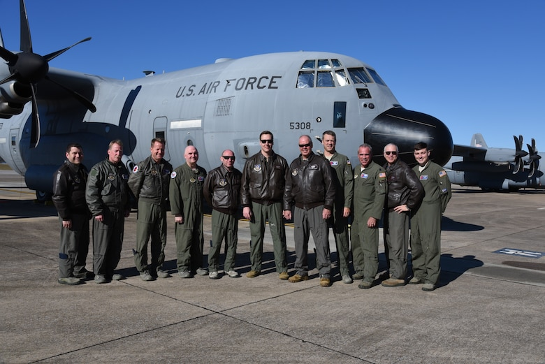 Lt. Col. David Price, 53rd Weather Reconnaissance Squadron evaluator navigator, poses with the crew after completing his 'fini' flight with the squadron. After 35 years, both active duty and reserve, Lt. Col. Price will retire having flown in the 403rd Wing for both the tactical missions and storm missions. (U.S. Air Force photo by Jessica L. Kendziorek)
