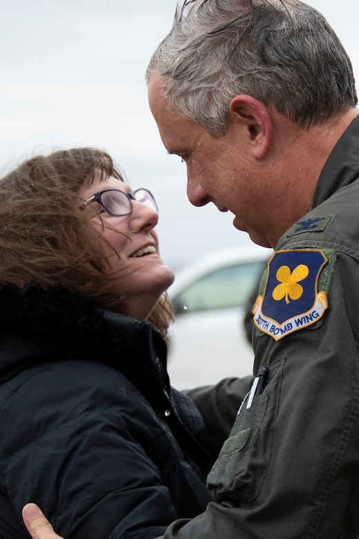 Col. Burgess and his wife hug on the flight line.