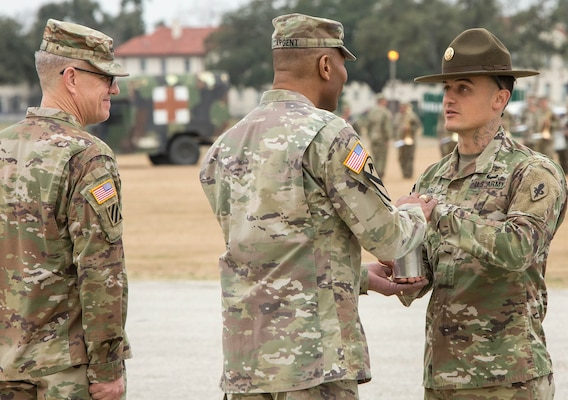 While Lt. Gen. James E. Rainey (left) looks on, Drill Sergeant David Nagel (right), U.S. Army Medical Center of Excellence Best Medic of the Year, presents Maj. Gen. Patrick D. Sargent the shell from the last round of salute as a memento of the change of command ceremony.