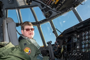 Capt. Tennison 'Wizard' Hunter, the pilot for a day from the 152nd Airlift Wing, Nevada Air National Guard,  poses for a photo in a C-130 Hercules cockpit Dec. 16, 2019. The Pilot for a Day program aims to support children with lifelong disabilities by welcoming them into the wing's military family and providing the child with the experience in being a U.S. Air Force pilot. (U.S. Air National Guard photo by Senior Airman Matthew Greiner)