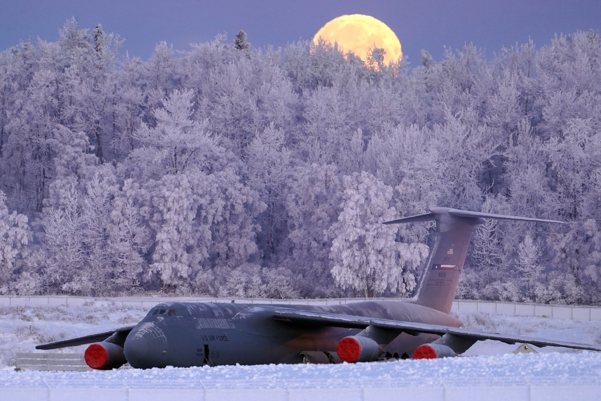 A large military aircraft sits on a runway surrounded by snow and  ice with the moon behind it.