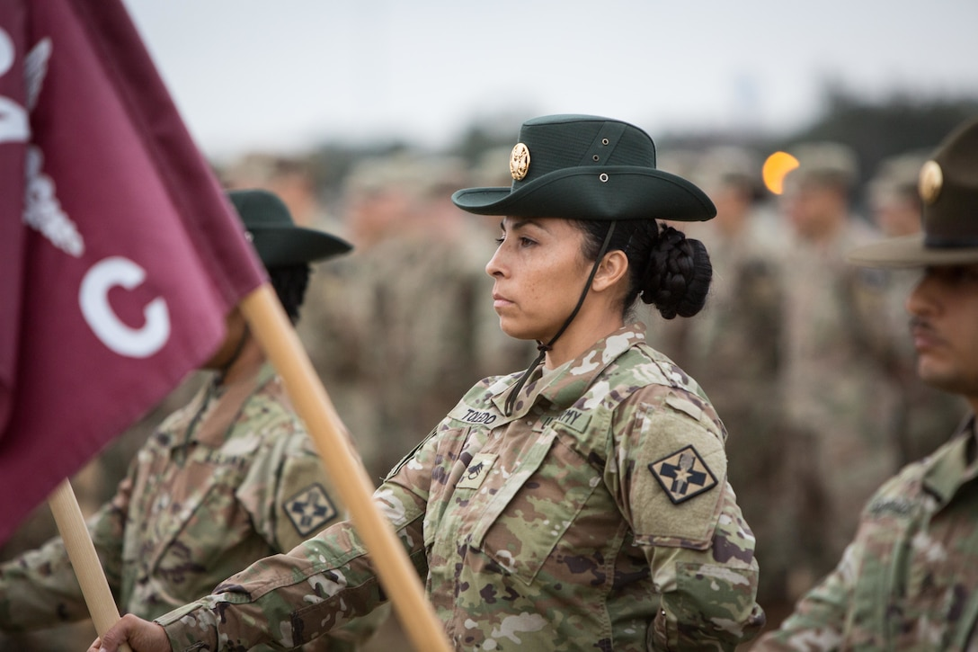 A soldier holds a flag while standing at attention during a ceremony.