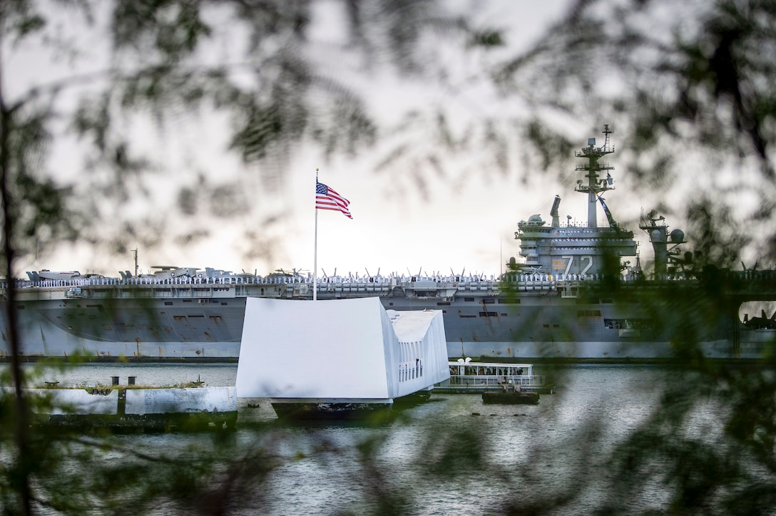 An aircraft carrier travels behind the USS Arizona Memorial, as seen through tree branches on nearby land.