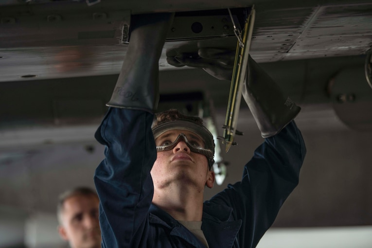 An airman wearing utility gloves and goggles looks up while working on an aircraft undercarriage.