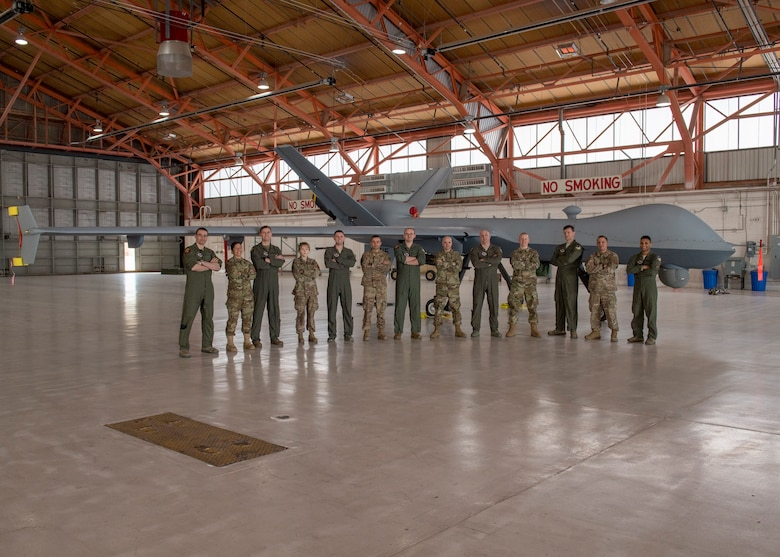 Some of the team who were directly involved the MQ-9 Reaper ferrying mission posed with the aircraft, Jan. 9, 2020, on Holloman Air Force Base, N.M. Airmen from the communications squadron, aircraft maintenance unit, and the 29th Attack Squadron were some of the members who ensured the success of ferrying an MQ-9 from California to Holloman. (U.S. Air Force photo by Airman 1st Class Autumn Vogt)