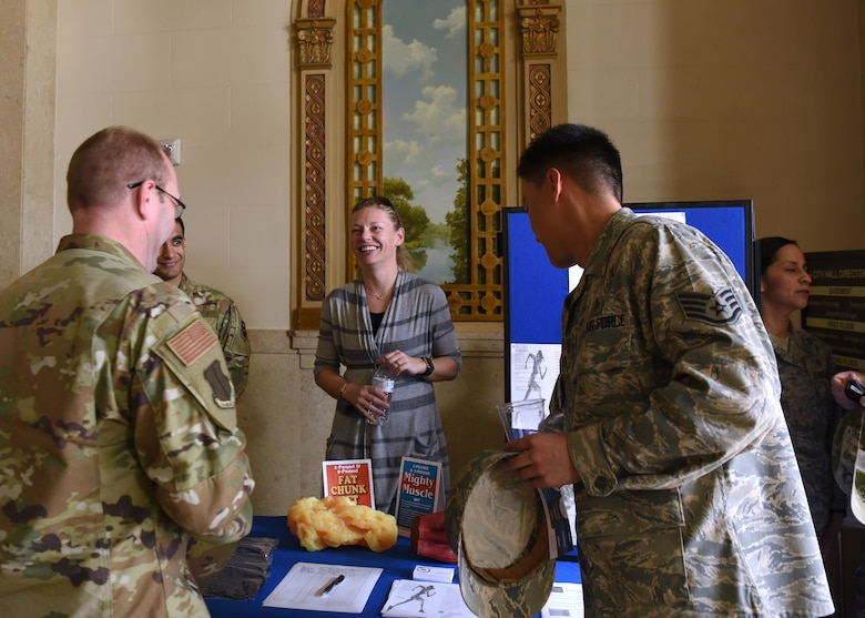 U.S. Air Force 17th Medical Group Health Promotion Coordinator Elizabeth Burmeister, engages with Goodfellow Air Force Base members at an information booth before a Commander's Call at the Murphey Performance Hall in San Angelo, Texas, Jan. 9, 2020. Burmeister encouraged individuals to sign pledges, giving up smoking or other unhealthy habits. (U.S. Air Force photo by Airman 1st Class Abbey Rieves)