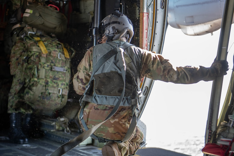 Loadmaster kneels by open side door aboard C-130J Super Hercules.