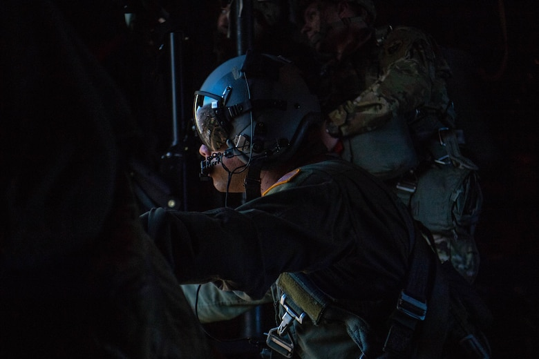 Loadmaster looks out side door aboard flying C-130J Super Hercules.