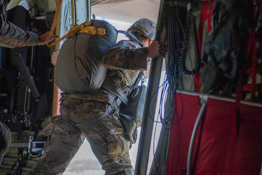 Soldier leans out side door midair aboard U.S. Air Force C-130J Super Hercules.